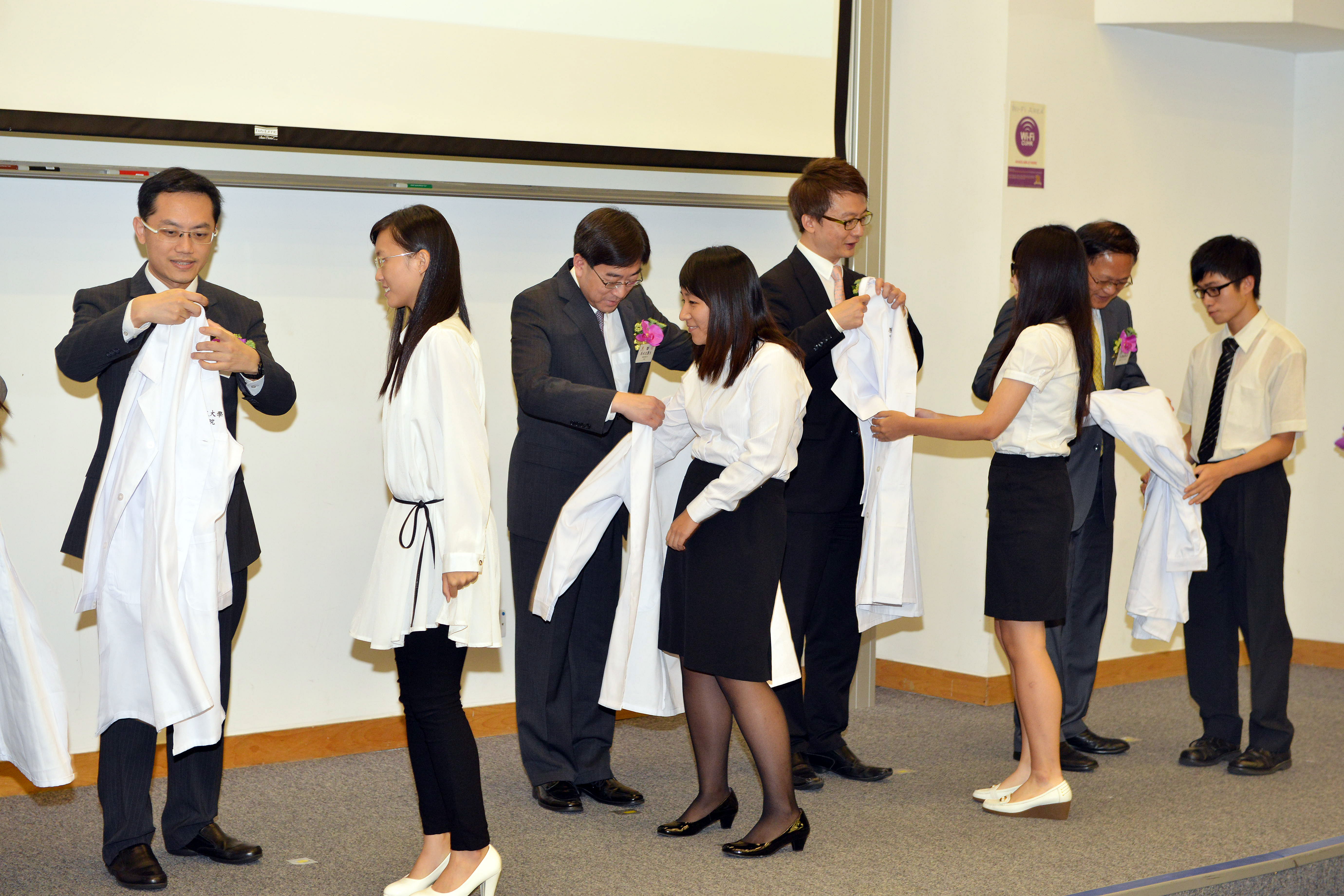 The officiating guests put the white coats on the Chinese medicine freshmen at the White Coat Ceremony.