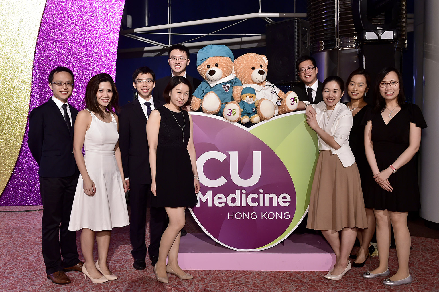 Guests take photo in front of the Faculty logo with medic and surgeon bears.